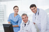 Cheerful doctors and surgeon looking at camera while working tog — Stock Photo