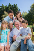 Multi generation family with a tablet pc sitting in park — Stock Photo