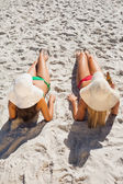 Attractive blonde and brunette in bikinis having beer — Stock Photo