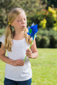 Young blonde girl blowing pinwheel — Stock Photo