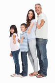 Portrait of a cute family in single file doing thumbs up at came — Stock Photo