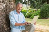 Smiling old man with a laptop — Stock Photo