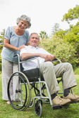 Smiling mature man in wheelchair with partner — Stock Photo