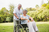 Mature woman in wheelchair with partner — Stock Photo