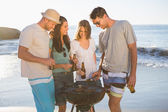 Cheerful young friends having barbecue together — Stock Photo