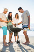 Happy young friends having barbecue together — Stock Photo