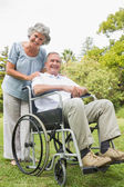 Cheeful mature man in wheelchair with partner — Stock Photo