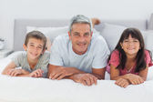 Father with his children lying on bed — Stock Photo