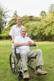 Happy man sitting in a wheelchair with his nurse pushing him — Stock Photo