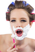 Young model in hair curlers posing while shaving — Stock Photo