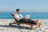 Young businessman lying on a deck chair with his laptop — Stock Photo