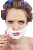 Serious model in hair curlers posing with shaving foam and razor — Stock Photo