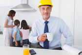 Father wearing hardhat and drinking coffee at home with his fami — Stock Photo