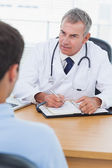 Serious doctor prescribing drug to his patient — Stock Photo