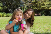 Daughter blowing bubbles with mother — Stock Photo