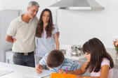 Cute siblings drawing together in kitchen with their parents smi — Stock Photo