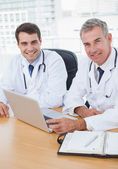 Doctors posing while working together on laptop — Stock Photo