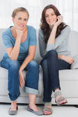 Relaxed women posing while sitting on the couch — Stock Photo