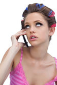 Thoughtful young model wearing hair rollers with phone — Stock Photo
