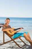 Cheerful handsome man strumming guitar — Stock Photo