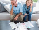 Stressed couple sitting on their couch paying their bills — Stockfoto