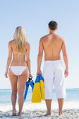Couple holding flippers and looking at the sea — Stock Photo