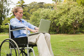 Young woman in a wheelchair with a laptop — Stock Photo