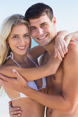 Sexy couple hugging and smiling at camera — Stock Photo