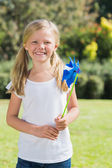 Blonde girl smiling and holding pinwheel — Stock Photo