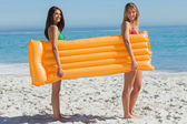 Two pretty friends holding air mattress — Stock Photo