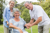Smiling woman in wheelchair with daughter and husband — Stock Photo