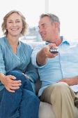 坐在沙发上看电视的快乐情侣 — 图库照片