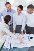 Happy architects interacting and analyzing plans together — Stock Photo