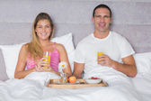 Happy young couple having breakfast in bed — Stock Photo