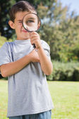 Small child looking through a magnifying glass — Stock Photo