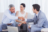 Salesman closing a deal with a smiling couple — Stock Photo
