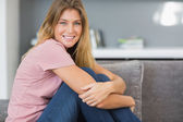 微笑着坐在她的沙发上的金发 — 图库照片