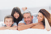 Cute family lying on bed and smiling at camera — Stock Photo
