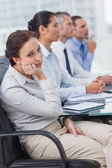 Bored businesswoman looking at camera while attending presentati — Stock Photo