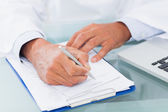 Hand of a doctor writing on a prescription — Stock Photo