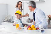 Boy trying on fathers hard hat with parents laughing — Stock Photo