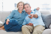 Happy couple cuddling and sitting on the couch watching tv — Stock Photo