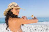 Attractive brunette with straw hat putting on sun cream — Stock Photo