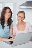 Mujeres sonrientes con el ordenador portátil — Foto de Stock