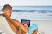 Handsome man scrolling on his tablet pc while sunbathing — Stock Photo