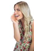 Seductive blonde wearing flowered dress telling secret — Stock Photo