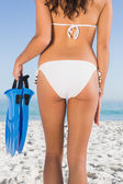 Perfect feminine buttocks of slim young woman holding fins — Stock Photo