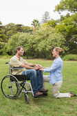 Happy man in wheelchair with partner kneeling beside him — Stock Photo