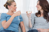 Women clinking their wine glasses while sitting on the sofa — Stock Photo