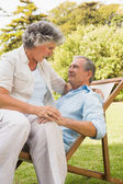 Happy mature couple sitting on sun lounger — Stock Photo